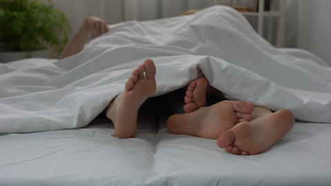 Legs of husband and wife making love in bed, couple intimate relations, sex Footage