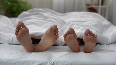 Womans feet flirting with man in bed, couple having intimate problem, relations Live Action