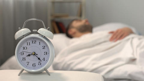 White clock near sleeping man bed, healthy morning habit, biorhythms, jet lag Live Action