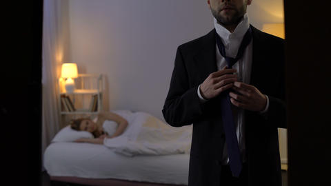 Young man putting on tie and going away, leaving sleeping mistress in hotel bed Footage