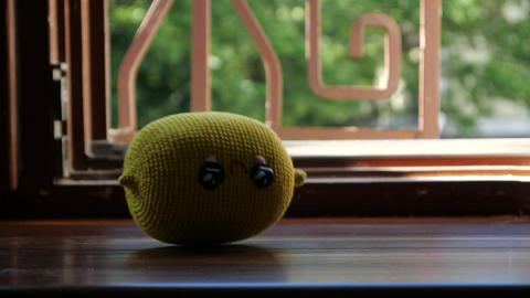 Toy Lemon falling on the wooden window sill - slow motion GIF