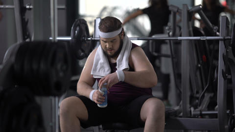 Obese male drinking water after barbell exercise, restoring aqua balance, diet Live Action