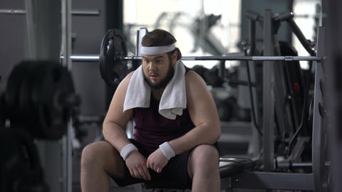 Funny overweight male pretending to be muscular and strong in gym, insecurities Live Action