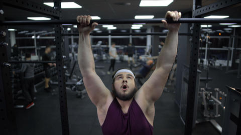 Overweight man trying to pull up on sport bar, weak body muscles, gym training Live Action