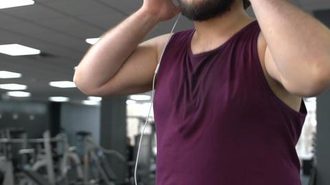 Inspired fat man in headphones walking on gym running track, endurance, health Footage