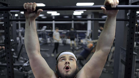 Weak obese male trying to pull up in gym, lack of self-confidence, insecurities Footage