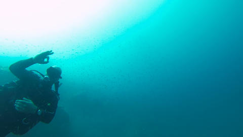 Recreational scuba diver swimming underwater, beckoning partner with ok gesture Live Action
