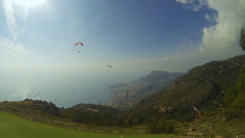 Couple of paragliders drifting over hills down towards seaside city, extreme Live Action