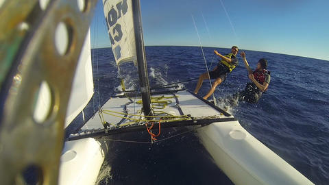 Catamaran under sail at high speed, people aside the hull high-fiving each other Live Action