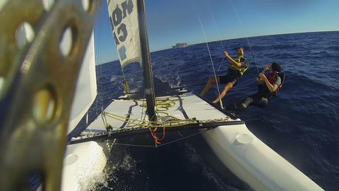 People moving across ocean on windsurfing catamaran, waving at ship on horizon Footage