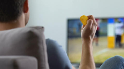 Emotional football fan watching match on TV at home, eating chips, back view Footage