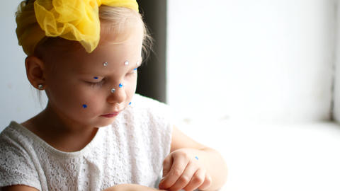 A beautiful little girl at the mirror makes herself a make-up Live Action
