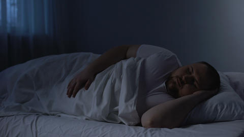 Fat sleeping man tossing in bed, health problem caused by excess weight, apnoe Live Action