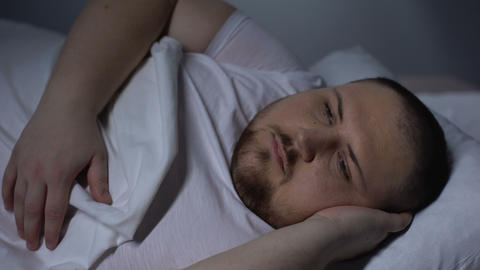 Overweight man in bed trying to fall asleep, health disorder, insomnia, anxiety Footage
