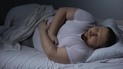 Fat man suffering from stomach pain at night, health problem, ulcer discomfort Footage