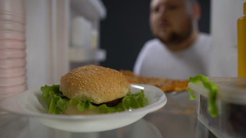 Addicted to fast food male eating fridge burger at night, unhealthy lifestyle Footage