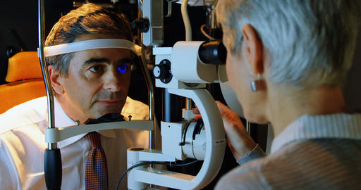 Optometrist examining patient eyes with slit lamp 4k Live Action