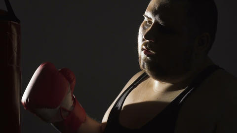 Fat man tired of fighting insecurities, breathing heavily after workout, slow-mo Live Action