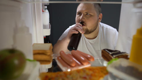 Fat male secretly taking beer bottle from fridge night, drinking with pleasure Live Action
