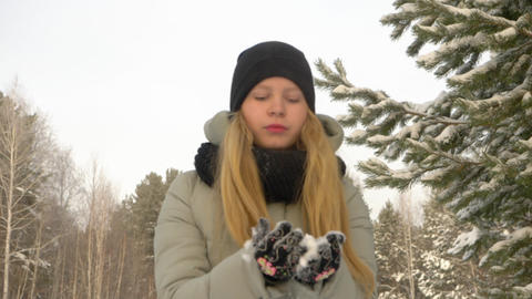 Young girl holding in hands snow. Girl blows and throws up snow in winter forest Footage