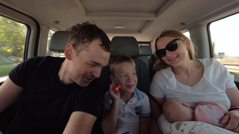 Happy parents with elder son and baby daughter having car journey Footage