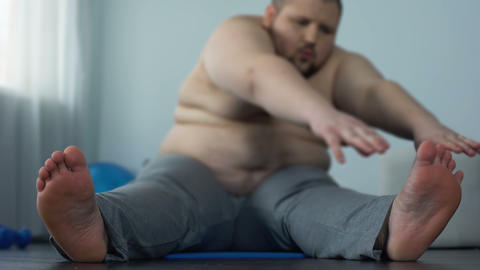 Stretching fat man reaching toes, weight loss decision, health and motivation Live Action