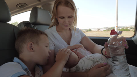 Family of mother, elder son and baby in the car Live Action