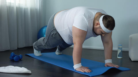 Fat male trying to do push up exercise at home, weak muscles, lack of motivation Live Action