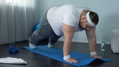 Fat male trying to do push up exercise at home, weak... Stock Video Footage