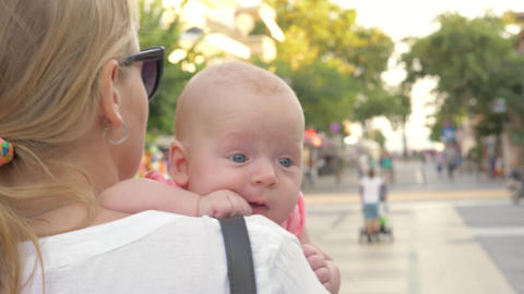 Baby having outdoor walk in mothers arms Live Action