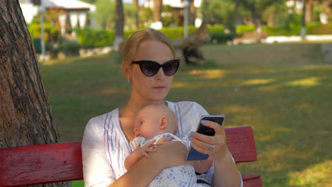 Woman using mobile during outing with baby in the park GIF