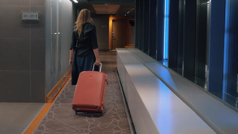 Woman with trolley case in the hotel hallway Footage