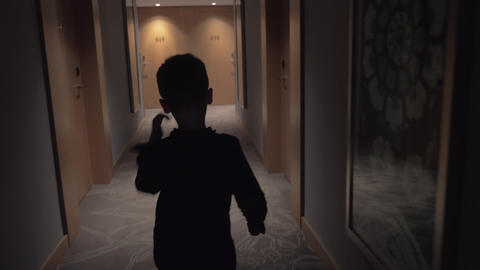 Child walking in hotel hall and opening room door with keycard Live Action