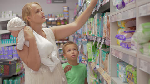 Woman with children buying diapers in the supermarket GIF