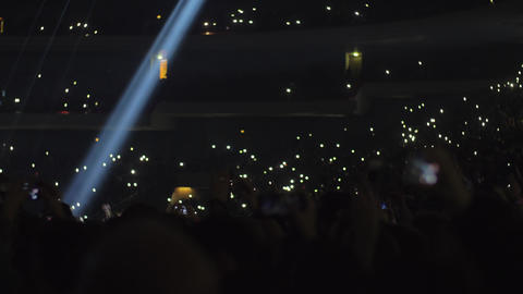 Crowded concert hall, music fans waving lights to music Live Action