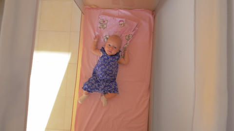 Three months baby girl lying in playpen Live Action