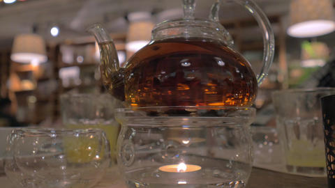 Glass teapot being heated with candle Live Action