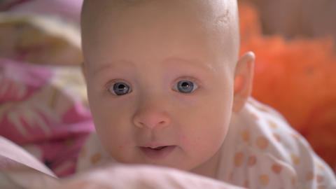 Portrait of baby girl with big blue smiling eyes Footage