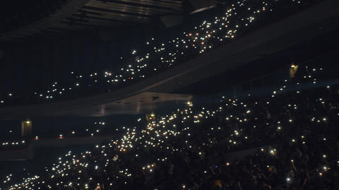 Crowded concert hall, people with lights in the darkness Live Action
