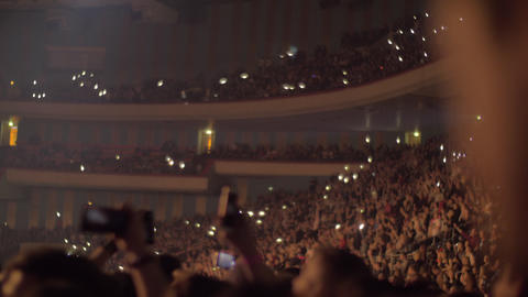 Audience waving hands and mobile flashlights at the concert Live Action