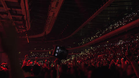 Audience dancing with lights at the concert Live Action