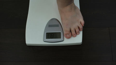 Man checking weight loss on scales, unhealthy nutrition, genetic predisposition Live Action