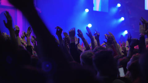 Hundreds of excited people dancing at the concert, view with bright stage lights Live Action
