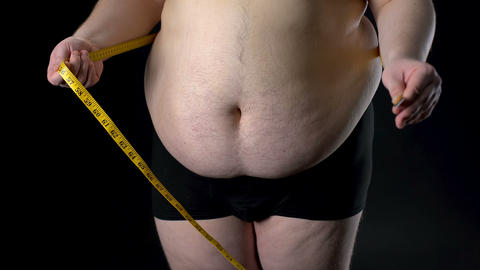 Overweight man measuring belly with tape, weight loss, unhealthy nutrition Live Action
