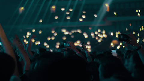 Music fans in concert hall waving lights and shooting with cellphones Footage