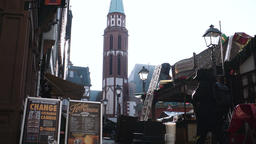 Frankfurt Christmas Market Shoppers and Old St. Nicholas Church Tower With Sunlight Peeking Through Footage