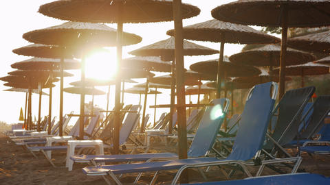 Empty chaise longues on resort and people leaving beach at sunset Footage
