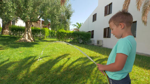 Child taking part in household duties and watering green lawn by the house Footage