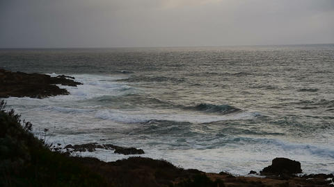 Waves by a rocky shore under an overcast sky in the winter Archivo