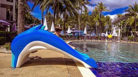 Boy sitting on slide near pool Archivo